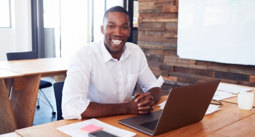 business man sitting at a desk with a laptop